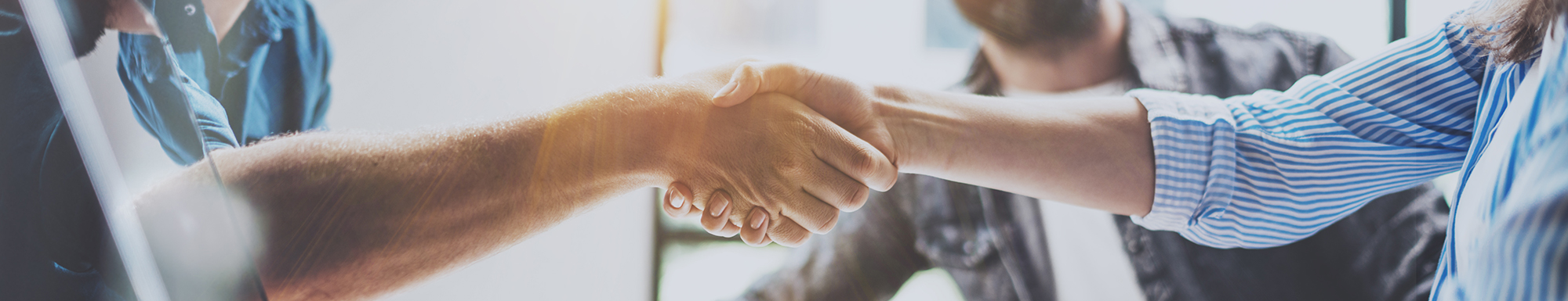 Man and woman shaking hands in business setting