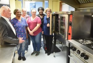 County Commission President Ed Hawkins talks with cooks and manager about the new equipment they got form funding form commission in photo left to right is Hawkins, Mary K. Layman, Kitchen food, Megan McDonald, Assistand Cook, Patricia Costello, Head Cook, Joy Thomas , Special Meals and Sara Bishop, manager Meals on Wheels.